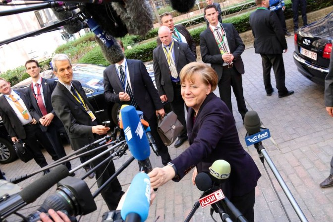 German Chancellor Angela Merkel, speaking ahead of the European Council in Brussels, Belgium, hands back a microphone that has fallen down.