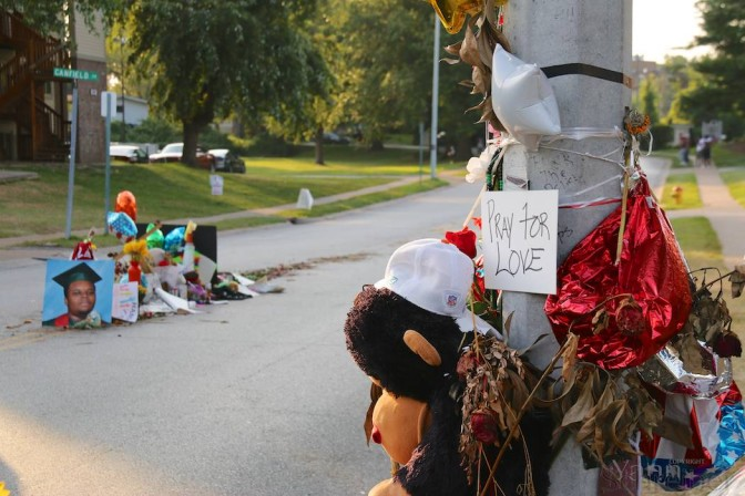 """The words """"Pray for Love"""" are attached to a pillar in Ferguson, MO, Monday August 25th, in what constitutes one of the three installations in memorial of Michael Brown, killed earlier this month. His picture can be seen behind as part of another memorial, in the middle of Canfield drive, on the spot he has been shot at by officer Darren Wilson, promoting days of unrest in the St Louis suburb. He has been buried on Monday, August 25th, after a service in St Louis, attended by family and civil rights activists. In the street, the night has been quiet as urged by the family, though people say the fight is """"not over yet"""". (Yann Schreiber)"""