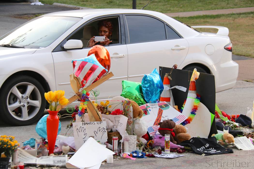 A women drives by flowers and placards in Ferguson, MO, Monday, August 25, 2014, in what constitutes one of the three installations in memorial of Michael Brown, killed earlier this month. This memorial is located in the middle of Canfield drive, on the spot he has been shot at by officer Darren Wilson, promoting days of unrest in the St Louis suburb. (Yann Schreiber)