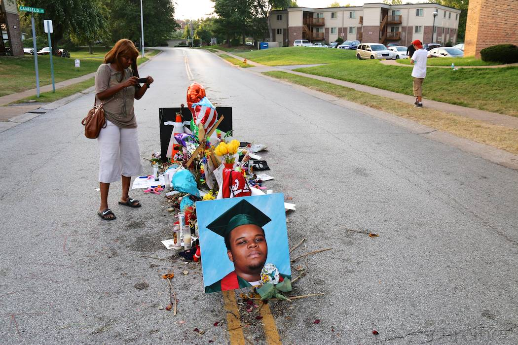 A women stands in front of flowers and placards in Ferguson, MO, Monday, August 25, 2014, in what constitutes one of the three installations in memorial of Michael Brown, killed earlier this month. This memorial is located in the middle of Canfield drive, on the spot he has been shot at by officer Darren Wilson, promoting days of unrest in the St Louis suburb. (Yann Schreiber)