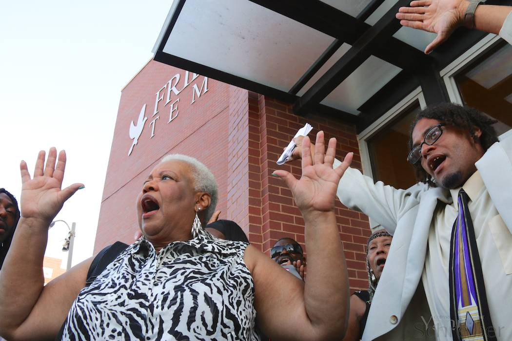 "A waiting crowd sings ""We Shall Overcome"" while raising their hands in reference to the ""Hands Up Don't Shoot"" slogan during the funeral service for Michael Brown in St Louis, MO, Monday, August 25, 2014. The service, held in the Friendly Temple Missionary Baptist Church, attracted thousands, including civil rights figures Al Sharpton and Jesse Jackson. (Yann Schreiber)"