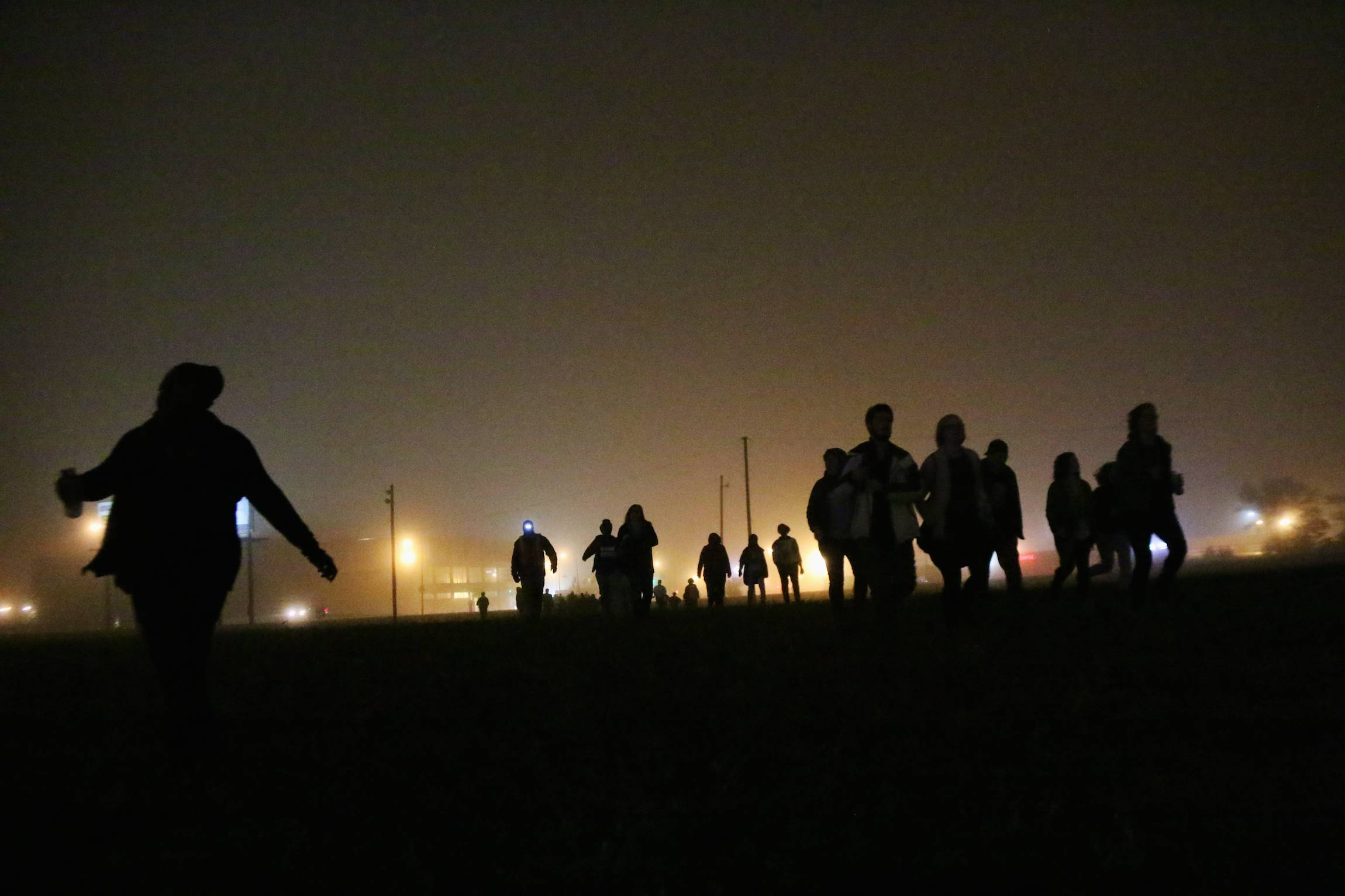Protesters run across a field in St. Louis, in the early hours of Monday, Oct. 13, 2014. The Sunday-night protest demanded justice for a series of police killings, including Michael Brown, shot by officer Darren Wilson in Ferguson, Aug. 9, 2014.