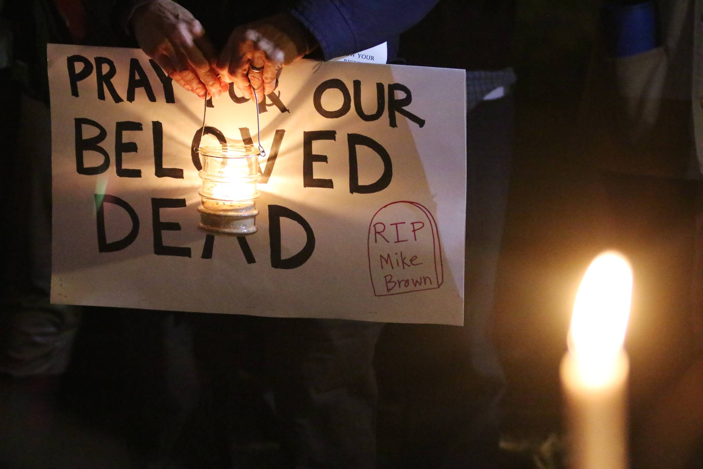 "A protester holds a sign, which reads ""pray for our beloved dead – R.I.P. Mike Brown"", at a candlelight vigil in Ferguson, Mo, Oct. 10, 2014."
