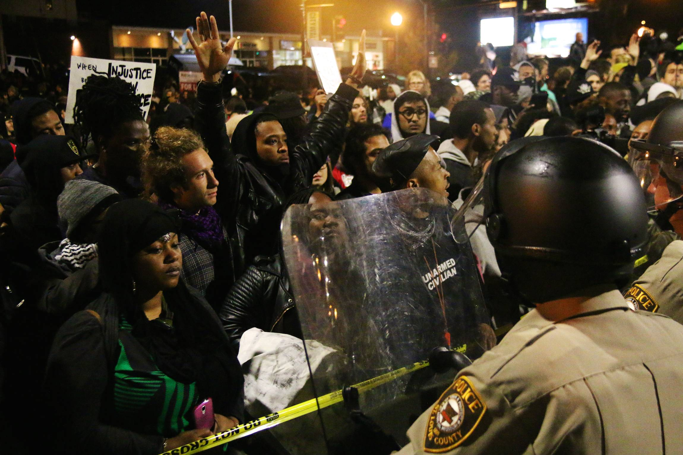 Protesters chant, raising their hands, in front of the police department in Ferguson, Mo, Oct. 11, 2014. The pose has become a symbol in the aftermath of the killing of Michael Brown, which sparked violent protests in the St. Louis suburb.