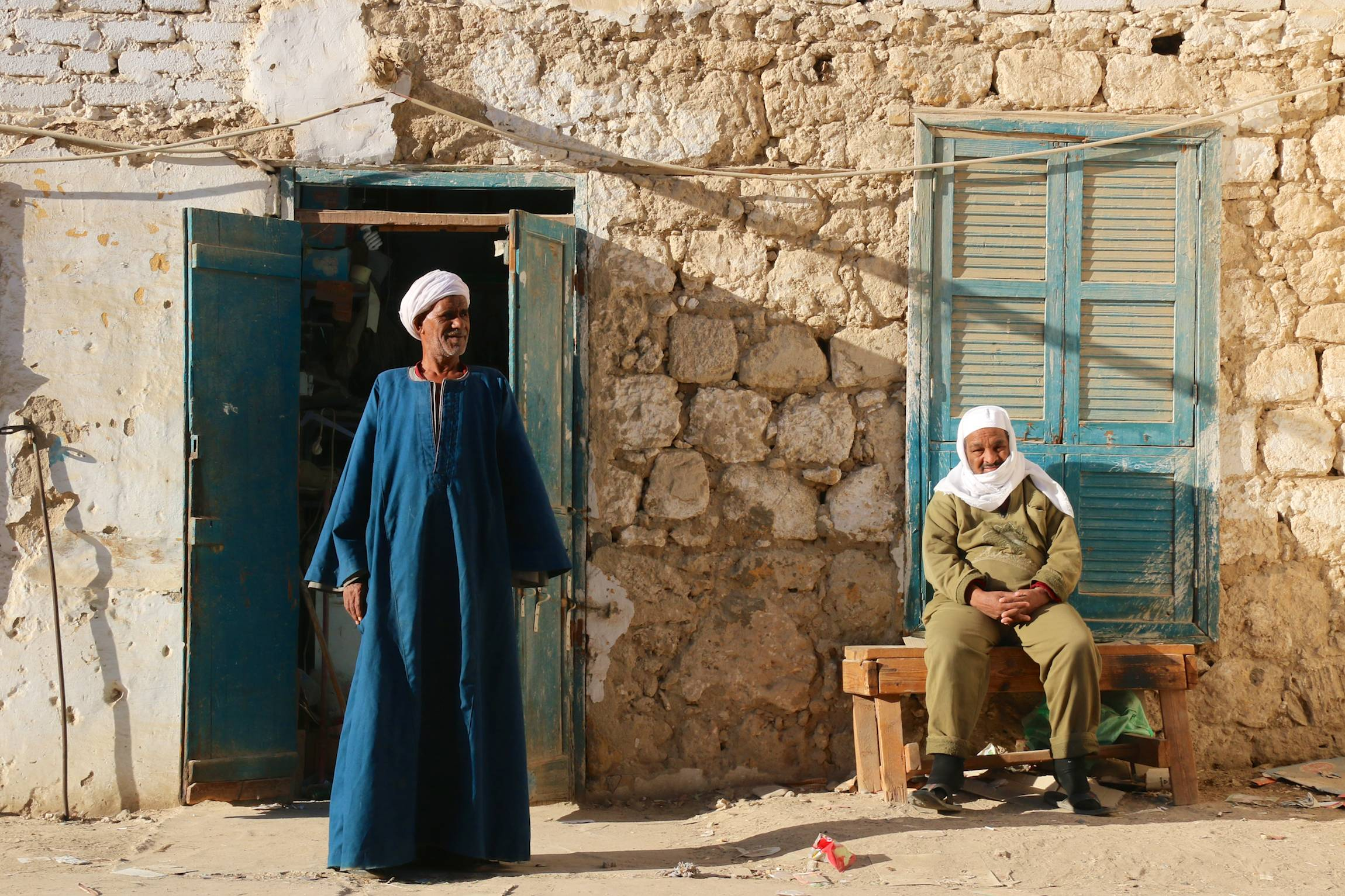 Man stand and sit in front of a house in El Quseir, Egypt, Jan. 8, 2014.