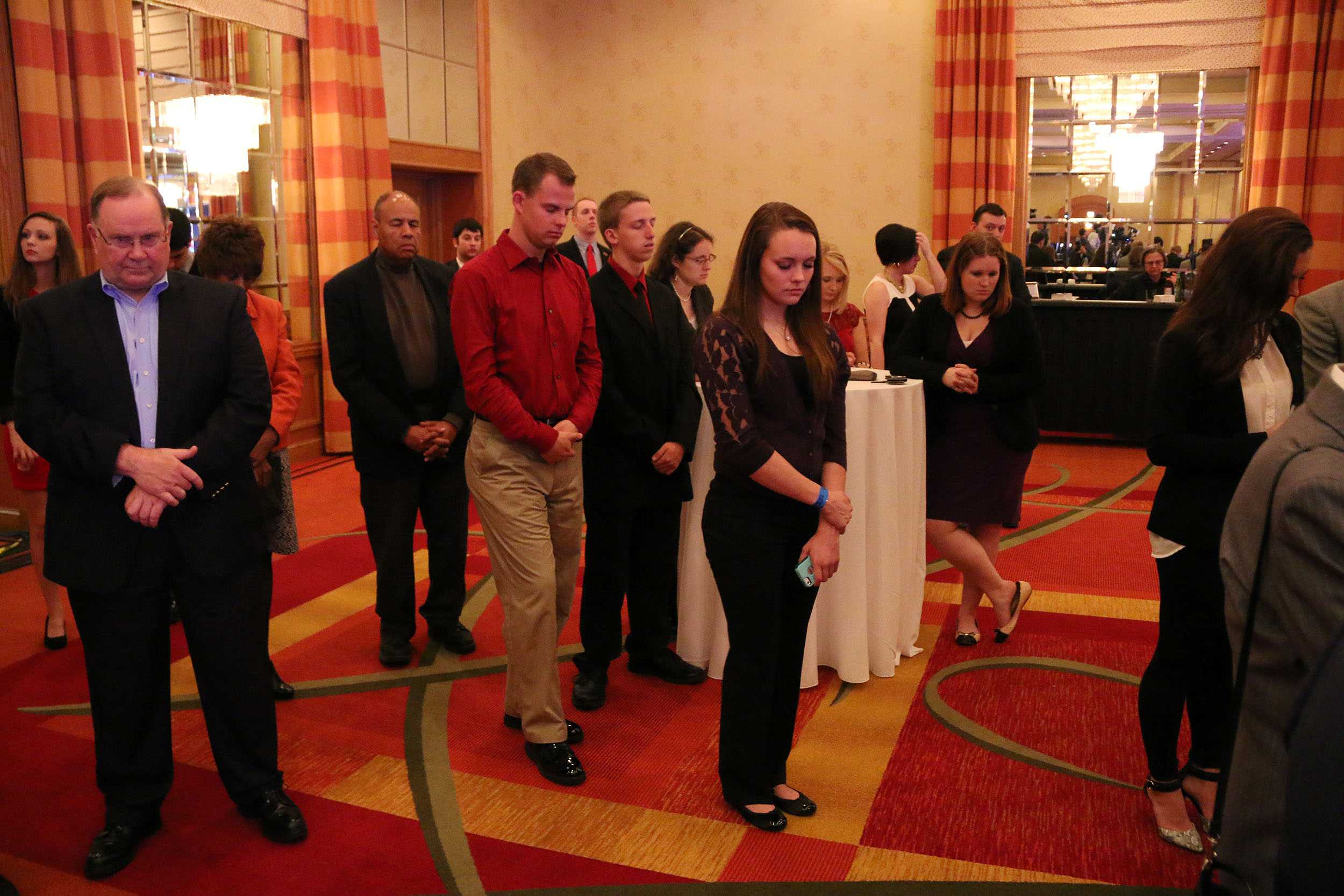 Guests stand and pray at the election night party of the Franklin County Republican party in the Renaissance Hotel in Columbus, Ohio, Tuesday, Nov. 2014.