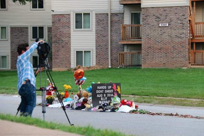 A reporter sets up a camera near the memorial for Michael Brown, Monday, August 25, 2014, in Ferguson, Mo. The death of the black teenager, who was shot by officer Darren Wilson, triggered days of violent protests in the St. Louis suburb. (Yann Schreiber, File)