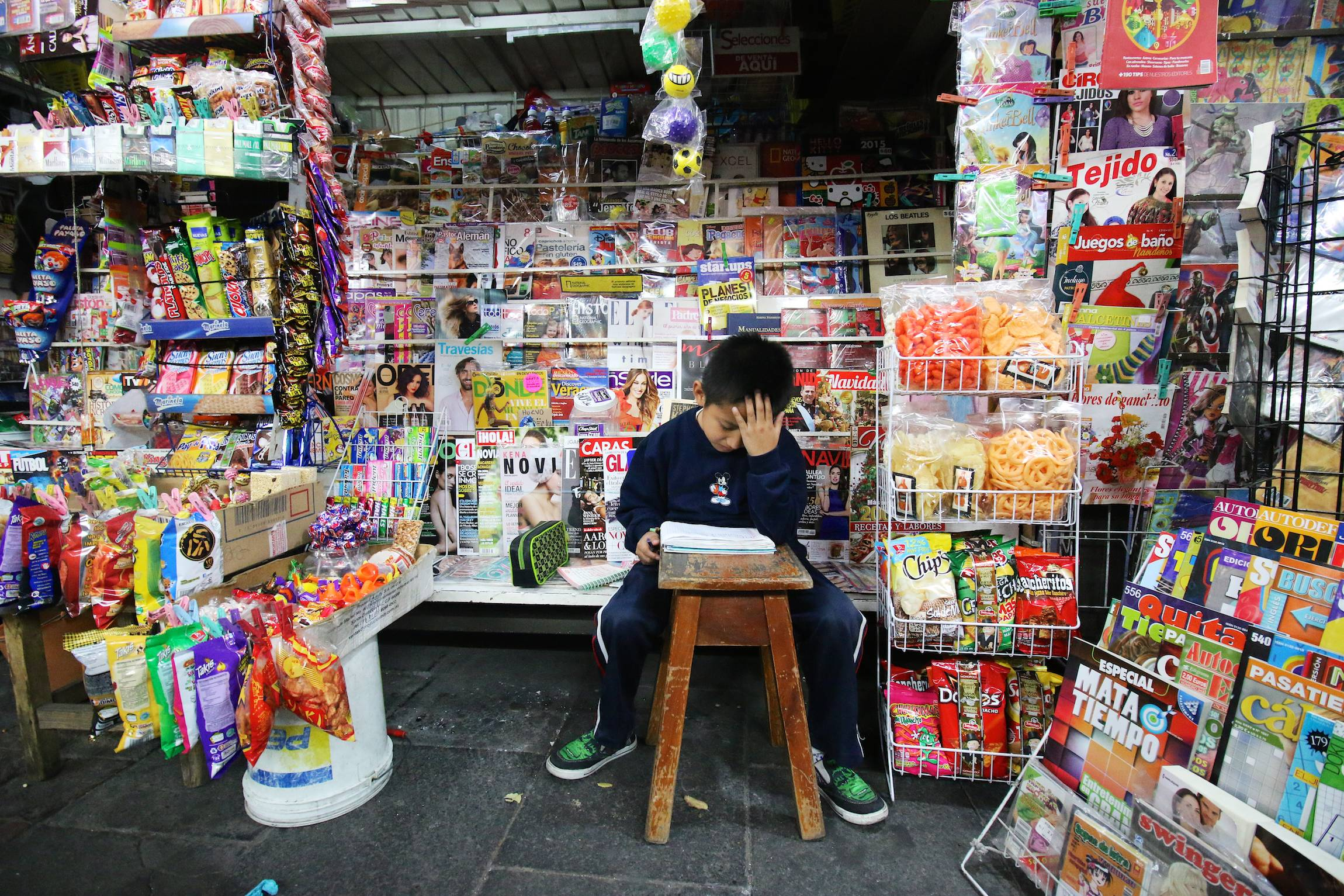 A boy studies, sitting in a kiosk in the streets of Mexico City, D.F., Friday, Nov. 21, 2014.