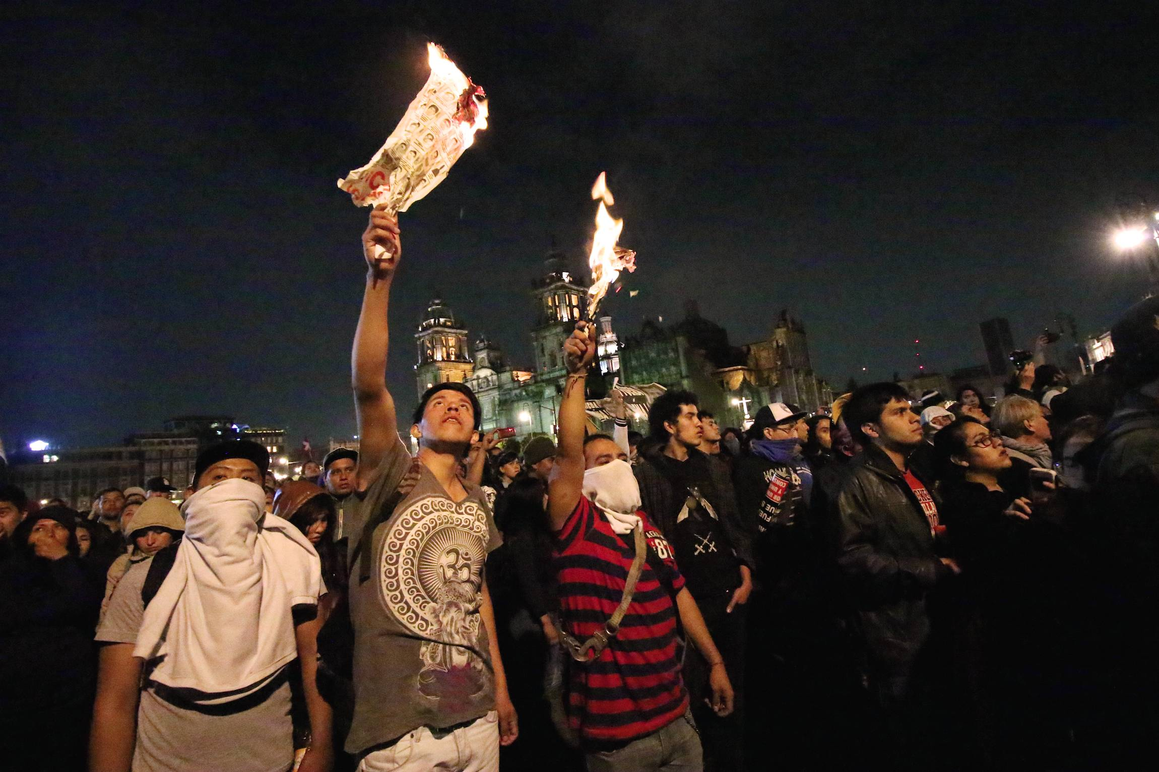 Protestors waive burning paper at a rally in Mexico City, D.F, Mexico, Thursday, Nov. 20, 2014. The rally followed similar, partly violent demonstrations in the country since the disappearance of 43 students in Guerrero State and was primarily against president Enrique Peña Nieto, asking him to step down.