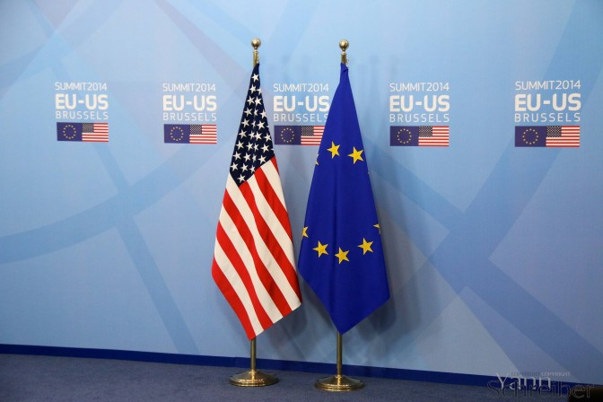 In this March 26, 2014, file photo, the U.S. and the European flag stand in the VIP entrance of the Berlaymont building in Brussels before for the EU-U.S. summit 2014. Photo: Yann Schreiber