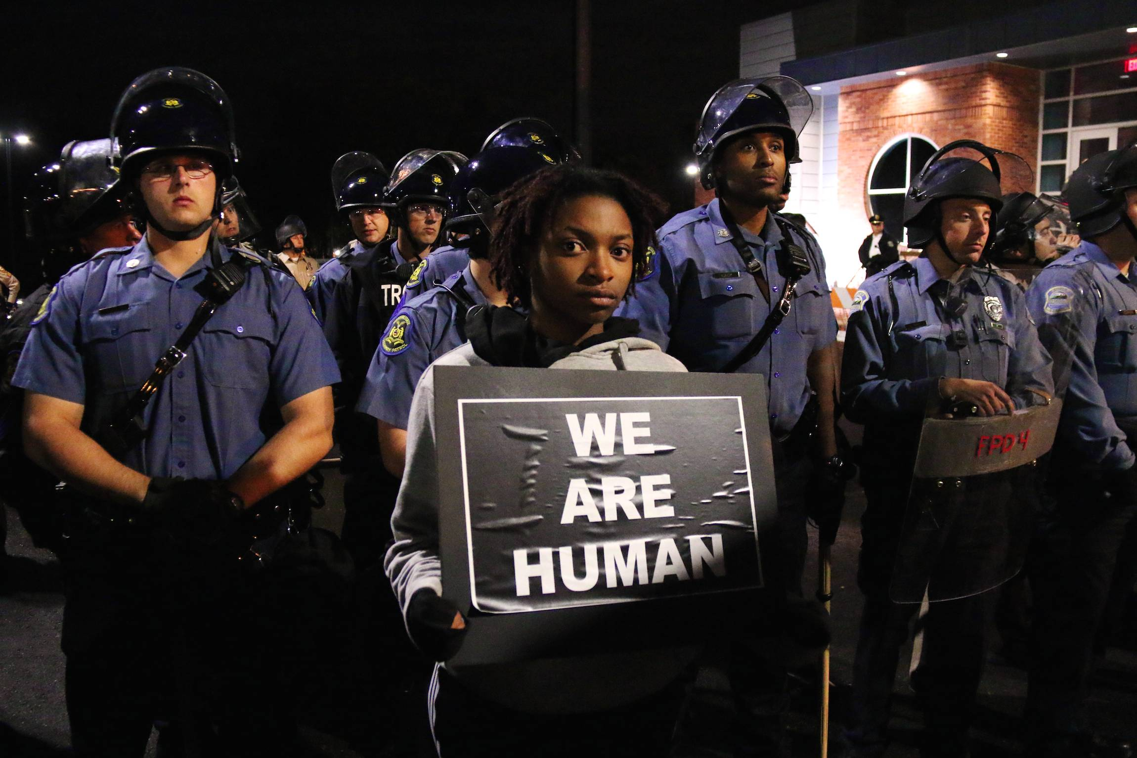 "A man holds a sign reading ""we are human"" during a standoff between police and protesters at the Ferguson Police Departement, in Ferguson, Missouri, Oct. 11, 2014."