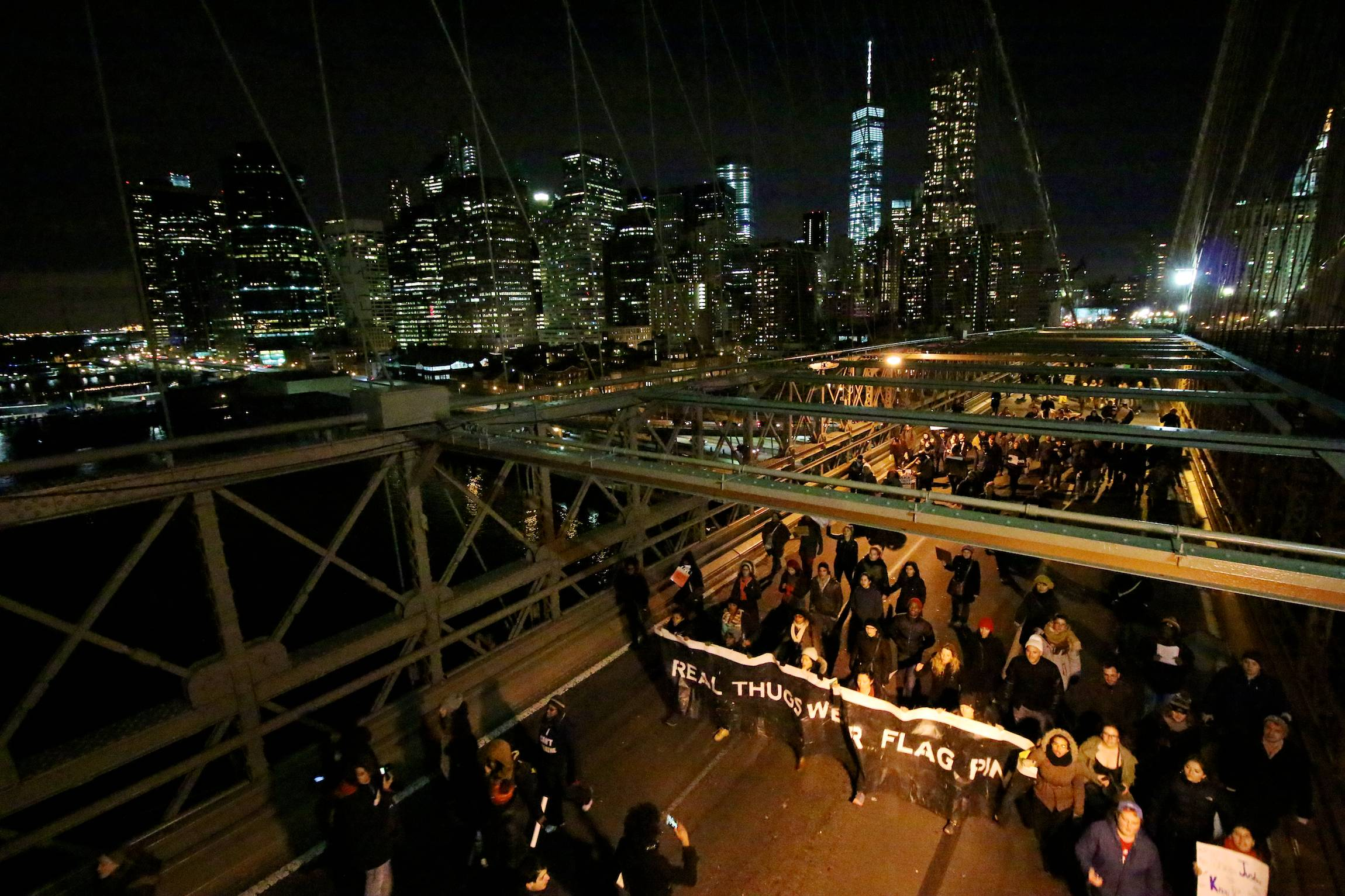 Protesters take to the streets on Brooklyn Bridge in New York to protest Grand Jury decisions not to indict policemen in the deaths of Michael Brown and Eric Garner, In New York City, Dec. 13, 2014, after an organized march earlier that day.