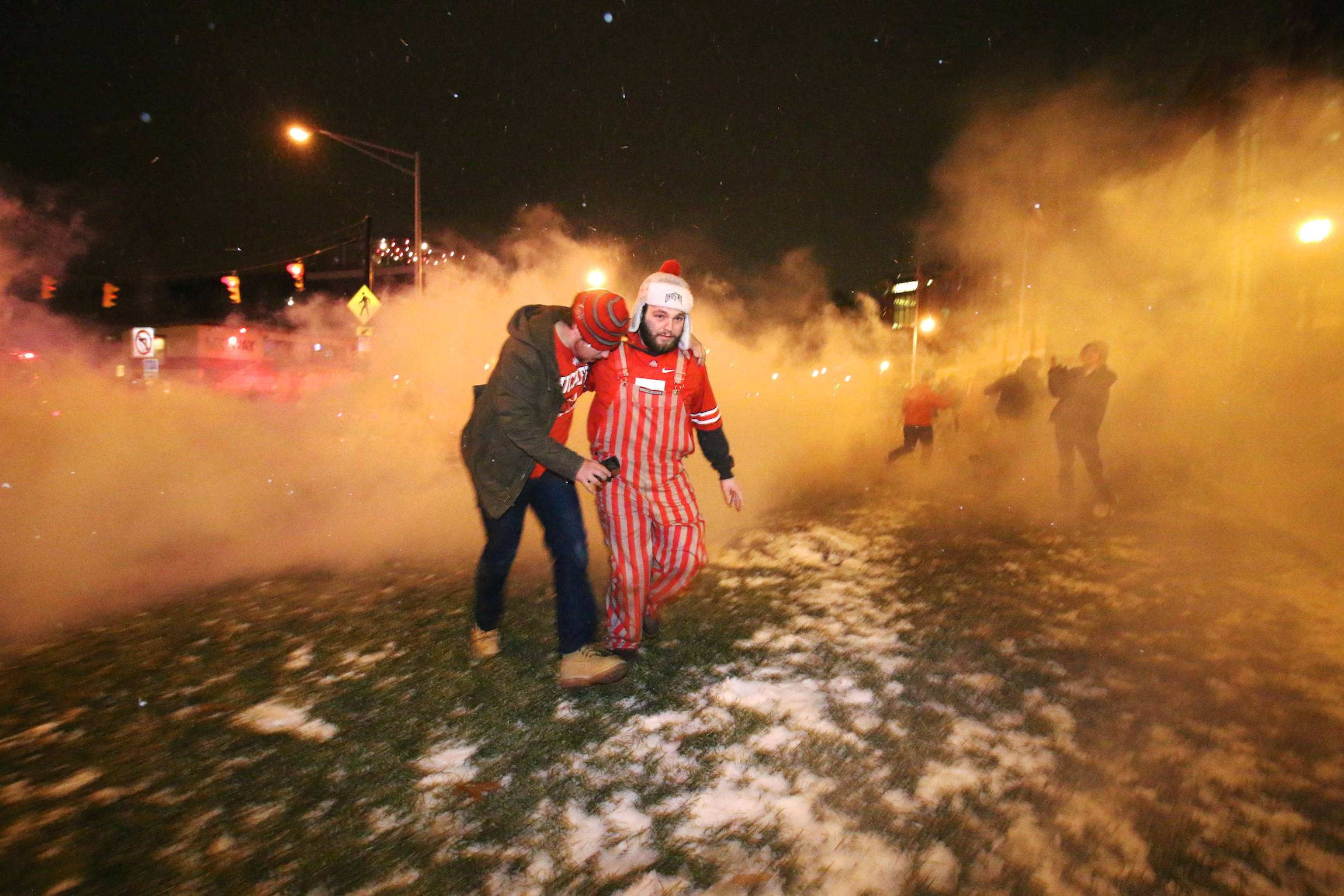 People walk away from clouds of tear gas in Columbus, Ohio, Jan. 12, 2015, as crowds took to the street to celebrate Ohio State's victory at the Football National Championship game in Texas.