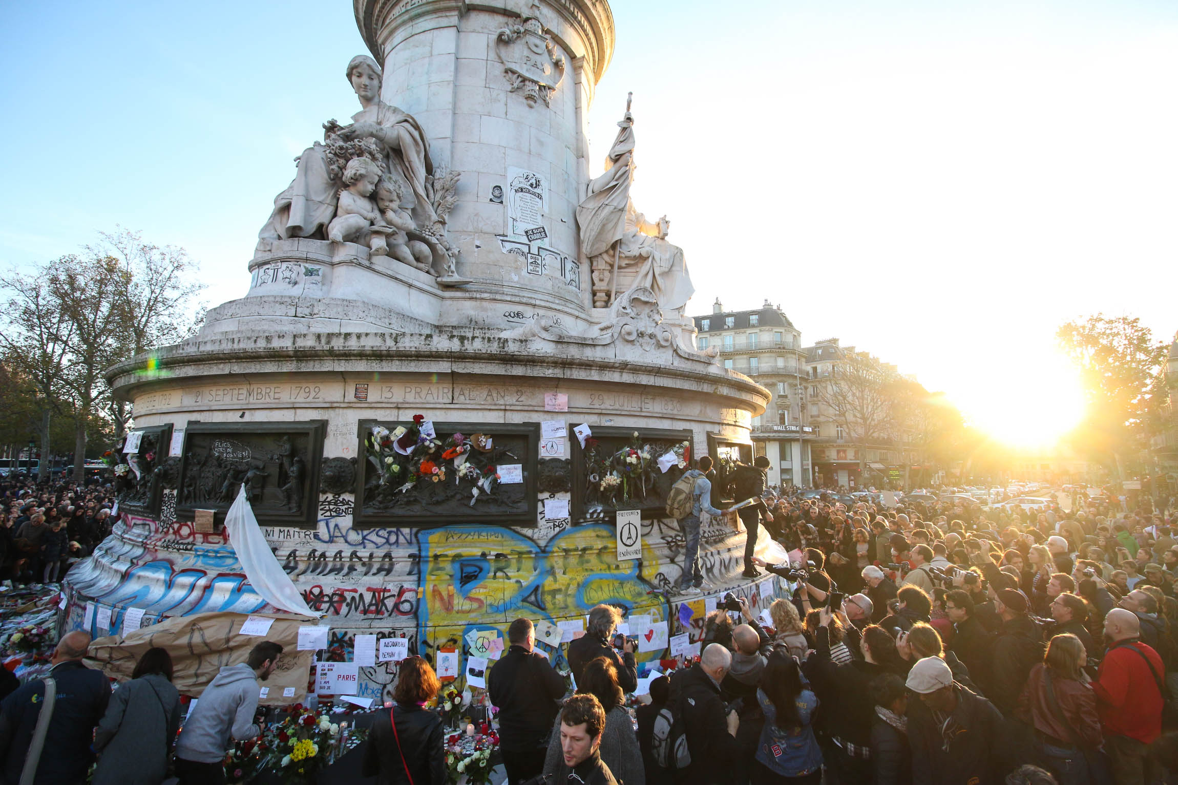 People lay flowers and paper with messages on Place de la Republique, Sunday, November 15, 2015.