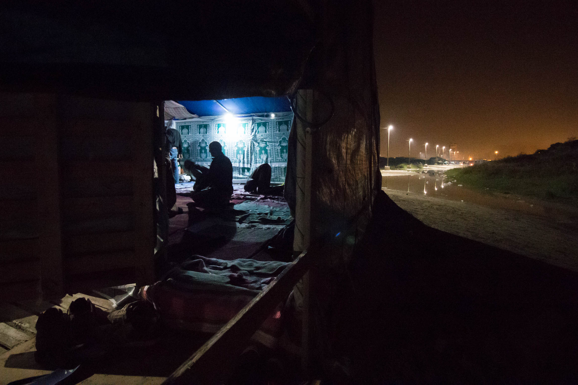 "Men pray after sunset in the main mosque at the ""New Jungle"" refugee camp in Calais, France, Sunday, October 5, 2015."