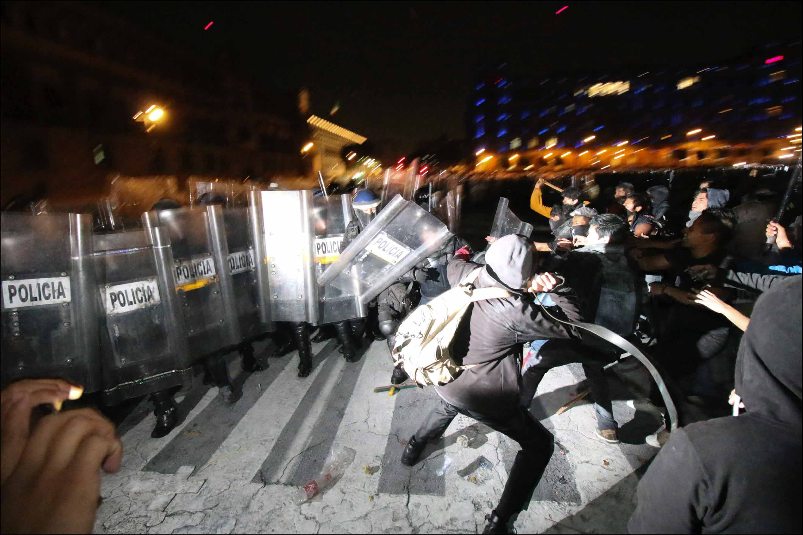 Mexican police and protesters clash at a rally in Mexico City, D.F, Mexico, Thursday, Nov. 20, 2014. The rally followed similar, partly violent demonstrations in the country since the disappearance of 43 students in Guerrero State and was primarily against president Enrique Peña Nieto, asking him to step down.