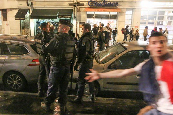 Un fan de football passe devant des gendarmes le 3 juillet 2016 à Paris.